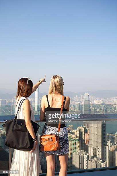 CONTENT] Two female tourists looking at view from Victoria peak Hong Kong