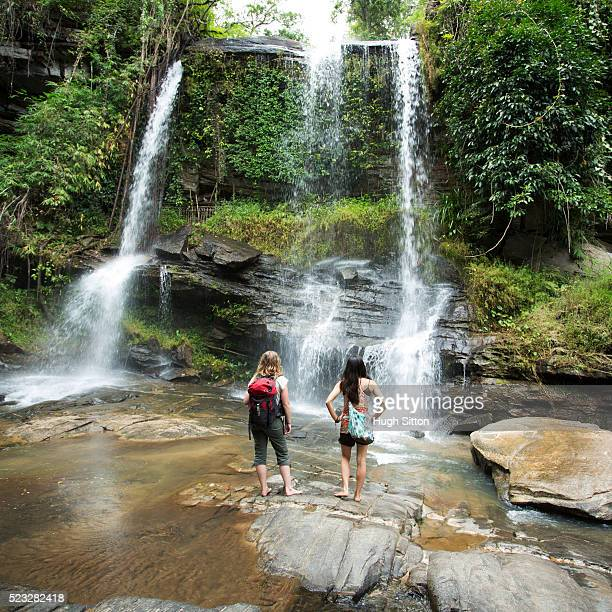 two female tourists looking at waterfall, chiang mai, thailand - hugh sitton stock pictures, royalty-free photos & images