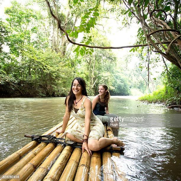 two female tourists on wooden raft, chiang mai, thailand - hugh sitton stock-fotos und bilder