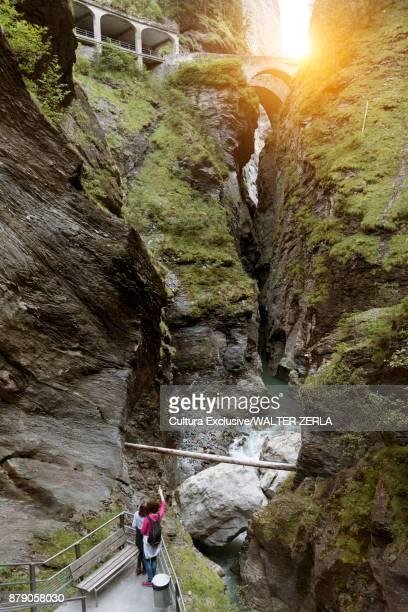 Two female tourists pointing up at bridges crossing Viamala Gorge, Graubunden, Switzerland