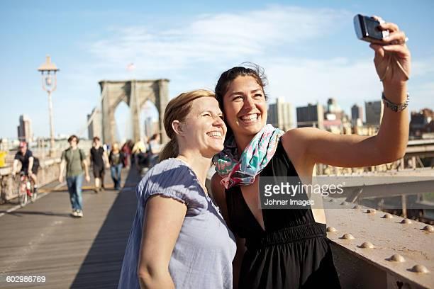 Two female tourists taking selfie on Brooklyn Bridge