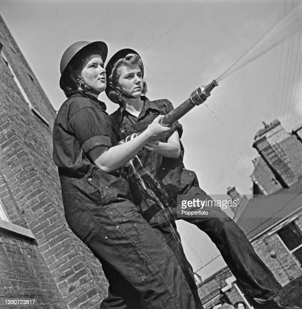 Two female trainee ward housekeepers practice with a water hose after setting up their own fire fighting service at the Royal Northern Hospital in...