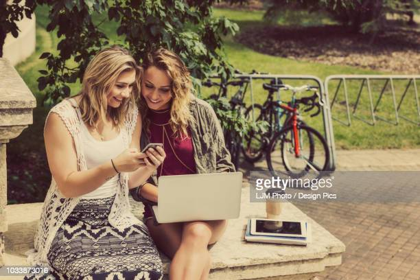 Two female university students sitting together and using their smart phone and laptop computer while sitting on the steps of a campus building