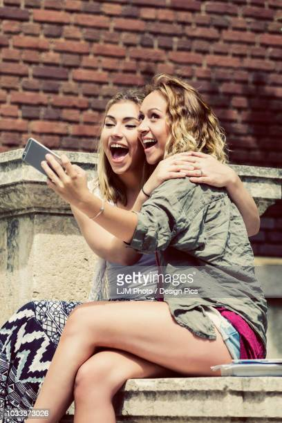 Two female university students sitting together on the campus, being silly and taking a self-portrait with their smart phone