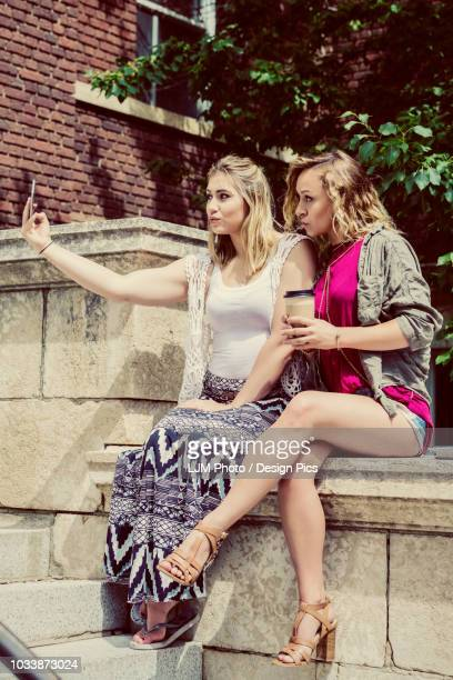 Two female university students sitting together on the campus taking a self-portrait with their smart phone and making silly pouty lips