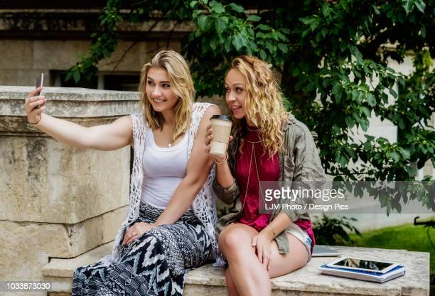Two female university students sitting together on the campus taking a self-portrait with their smart phone