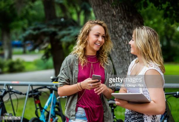 Two female university students standing and talking together beside a bike rack on campus