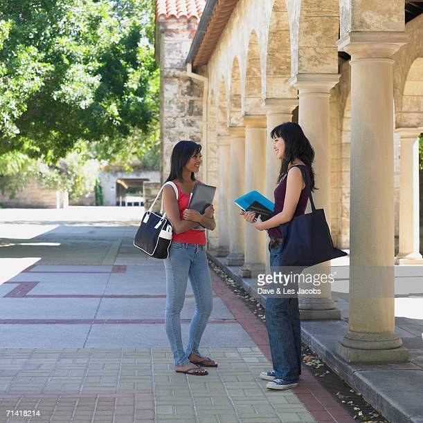 Two female university students talking on campus