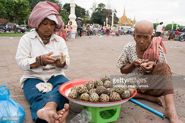 Two female vendor eating fruit and counting money on a street in Phnom Penh Southcentral Region Cambodia