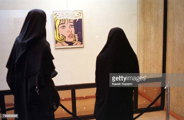 Two female visitors fully covered in Islamic black chador viewing 'The Melody Haunts My Reverie' by American Pop Artist Roy Lichtenstein on display...