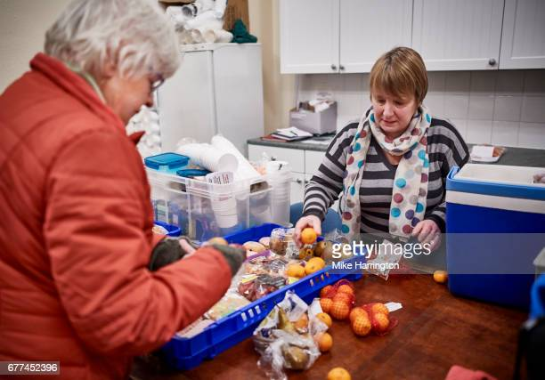 two female volunteers preparing food for soup kitchen - homelessness stock pictures, royalty-free photos & images