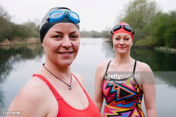 two female wild swimmers laughing by a lake - winning stock pictures, royalty-free photos & images