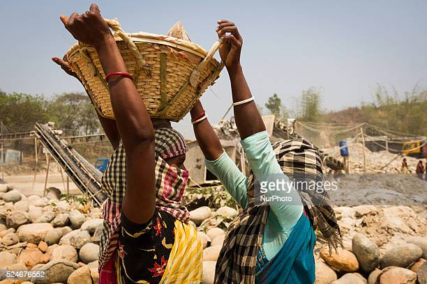Two female workers helping each other for carrying stones to the crashing machine in a Stone Crashing Plant in Sylhet Bangladesh A huge percentage of...