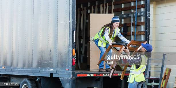 Two female workers with a truck, moving furniture