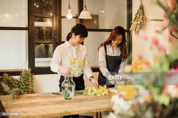 Two female workers working in green shop.