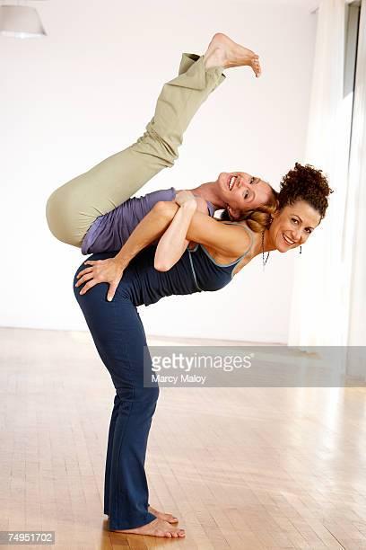 two female yoga teachers posing, smiling, portrait - 人の背中 ストックフォトと画像