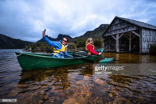 Two females canoeing around the famous boat shed on Dove Lake at Cradle Mountain.