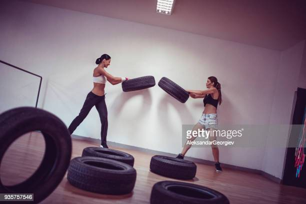 two females doing strength exercise with tires in the gym - military style stock pictures, royalty-free photos & images
