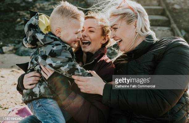 two females holding a happy little boy on the beach - politics and government stock pictures, royalty-free photos & images