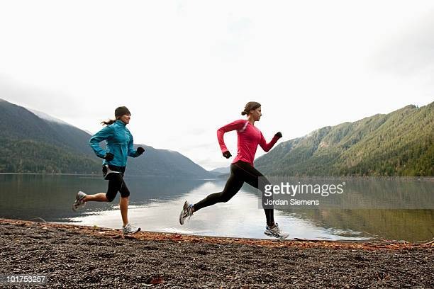 two females jogging together along the shore of lake crescent. - cross country running stock pictures, royalty-free photos & images