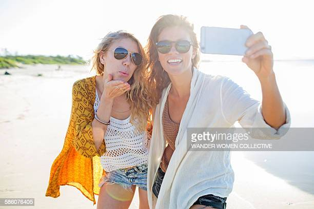 Two females on beach in Byron Bay taking selfie