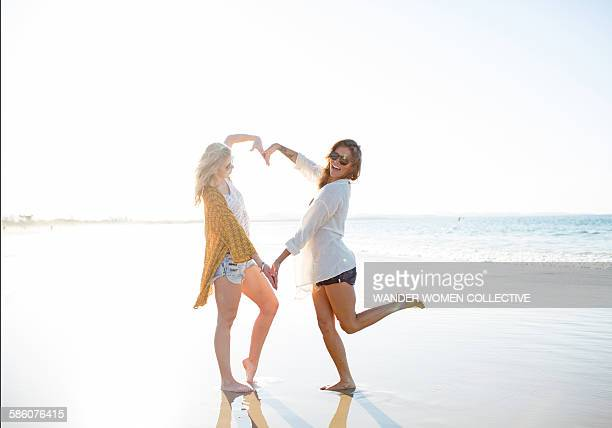 Two females on beach making heart shape with arms