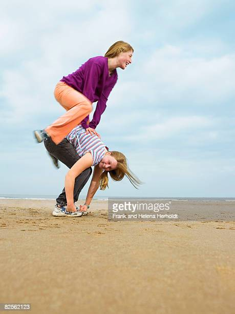 Two females playing leap-frog on beach