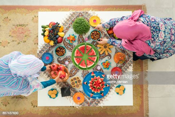 two females preparing food decorated table - ramadan stock pictures, royalty-free photos & images