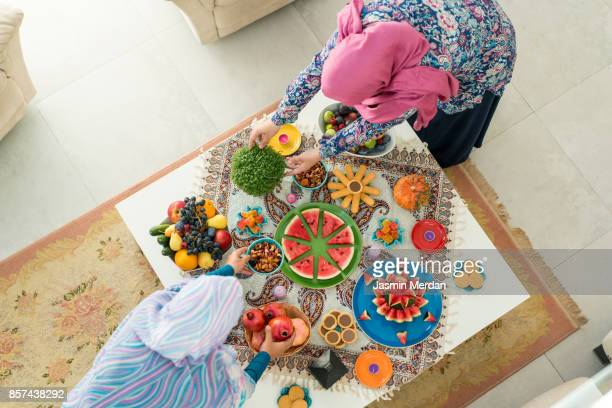 Two females preparing food decorated table