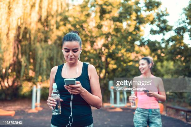 two females setting up their workout playlists - colors soundtrack stock pictures, royalty-free photos & images