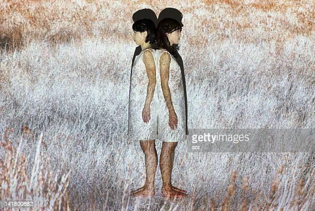 Two females standing back to back in grassy plain
