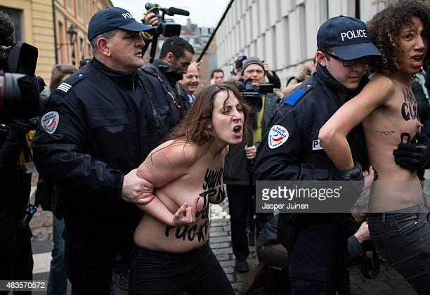 Two Femen activists are detained by policemen after jumping in front of the car with former IMF chief Dominique StraussKahn upon his arrival for his...
