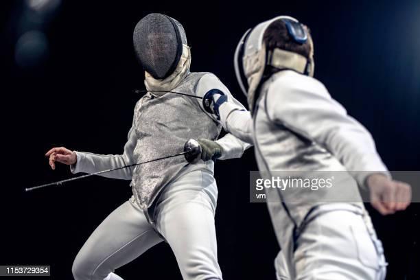 twee omheiningen duelleren - degenschermen stockfoto's en -beelden