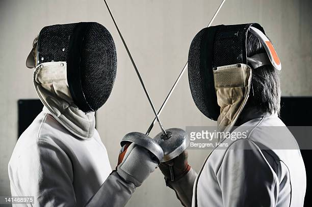 Two fencers face to face in sports hall