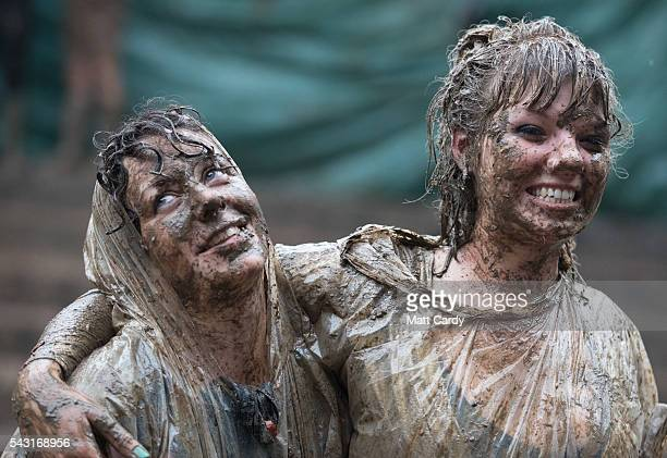 Two festival goers roll in the mud after they took part in a tomato fight at the Glastonbury Festival 2016 at Worthy Farm Pilton on June 25 2016 near...