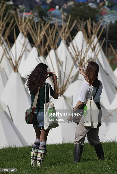 Two festival goers take a photograph of the tipi field as music fans start to arrive at the Glastonbury Festival site at Worthy Farm, Pilton on June...