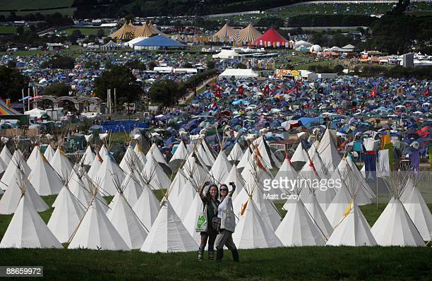 Two festival goers take a photograph of themselves in front of the tipi field as music fans start to arrive at the Glastonbury Festival site at...