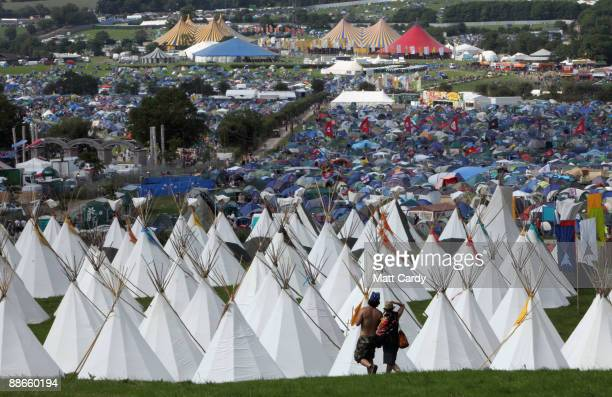 Two festival goers walk in front of the tipi field as music fans start to arrive at the Glastonbury Festival site at Worthy Farm, Pilton on June 24,...