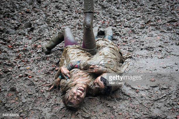 Two festival revellers roll in the mud after they took part in a tomato fight at the Glastonbury Festival 2016 at Worthy Farm Pilton on June 25 2016...