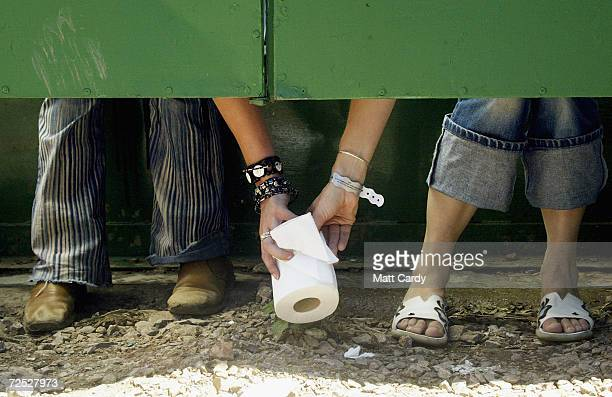 Two festivalgoers pass a roll of toilet paper between toilet cubicles during the 2004 Glastonbury Festival on June 25 2004 at Worthy Farm Pilton...