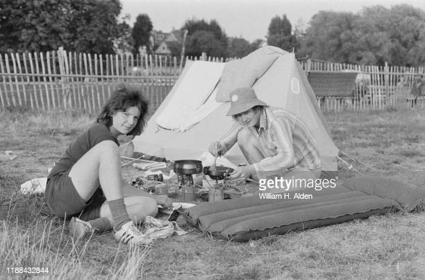 Two festival-goers preparing food outside their tent at the campsite of Reading Festival a day before the official start, Richfield Avenue, Reading,...