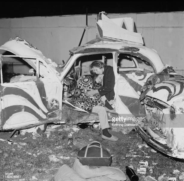 Two festivalgoers relaxing on a wrecked car art installation at Isle of Wight Festival Wootton UK August 1969