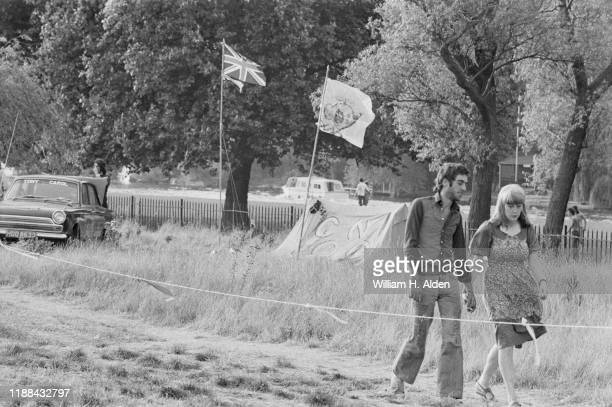 Two festival-goers walk hand in hand at the campsite of Reading Festival a day before the official start, Richfield Avenue, Reading, UK, 26th August...