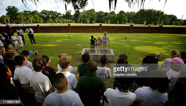 Two fifth graders from the Lady's Island Intermediate School place a wreath at a plaque at the Beaufort National Cemetery marking the mass grave of...