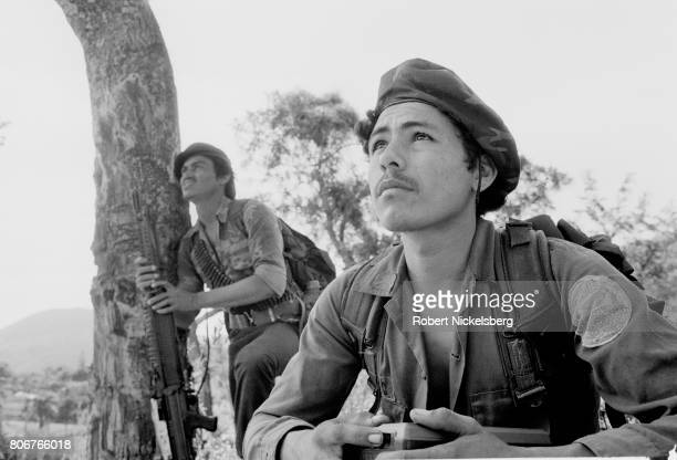Two fighters from the Farabundo Martí National Liberation Front watch a low flying military observation plane June 19, 1983 in Jucuarán, El Salvador....