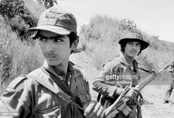 Two fighters from the Farabundo Marti National Liberation Front watch a low flying Salvadoran military observation plane in Jucuarán El Salvador June...