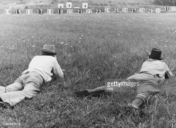 Two figures in the prone position aiming rifles at targets shaped like men, students learn to use different types of rifles and shotguns as they are...