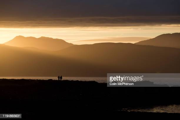 Two figures silhouetted against the mountains on the island of Mull at sunset on neighbouring Easdale island Easdale was Scotland's smallest...