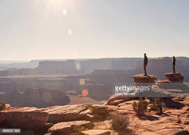Two figures stand at the canyons edge, Dead Horse Point State Park, Utah.
