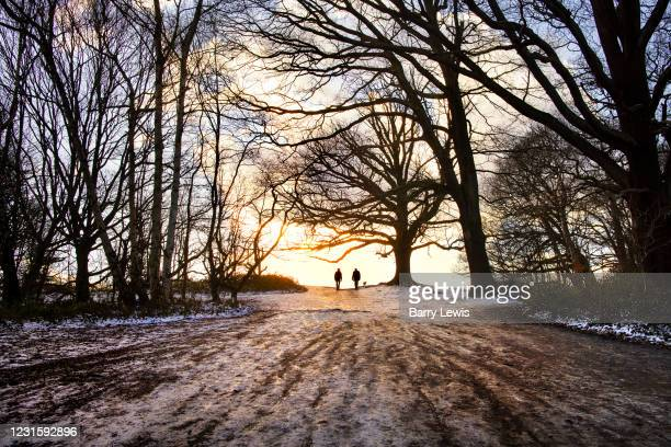 Two figures walking in the snow in Hampstead Heath on 24th January 2021 in London, United Kingdom.